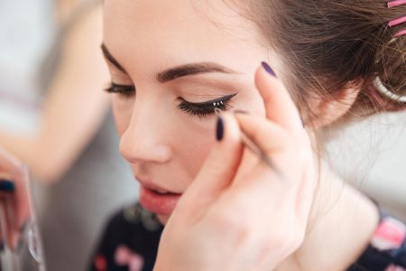 makeup-artist-doing-false-lashes-to-young-woman-P4QGWXY